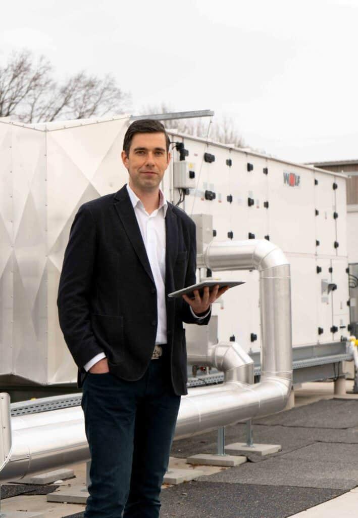 Projektleiter Melnikov auf dem Dach der Turnhalle - im Hintergrund ist die Belüftungsanlage zu sehen